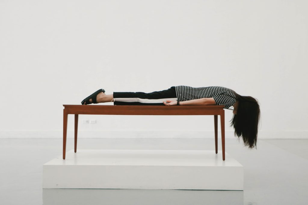 Woman laying facedown on a table looking defeated