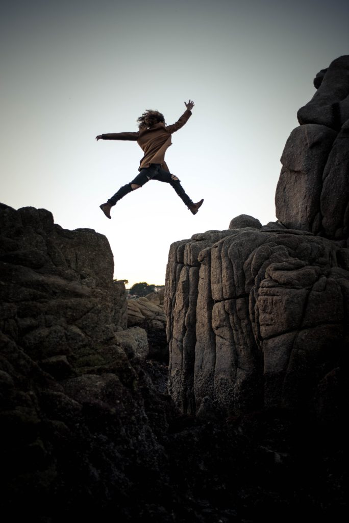 Woman leaping from one rock ridge to the next, arms outstretched