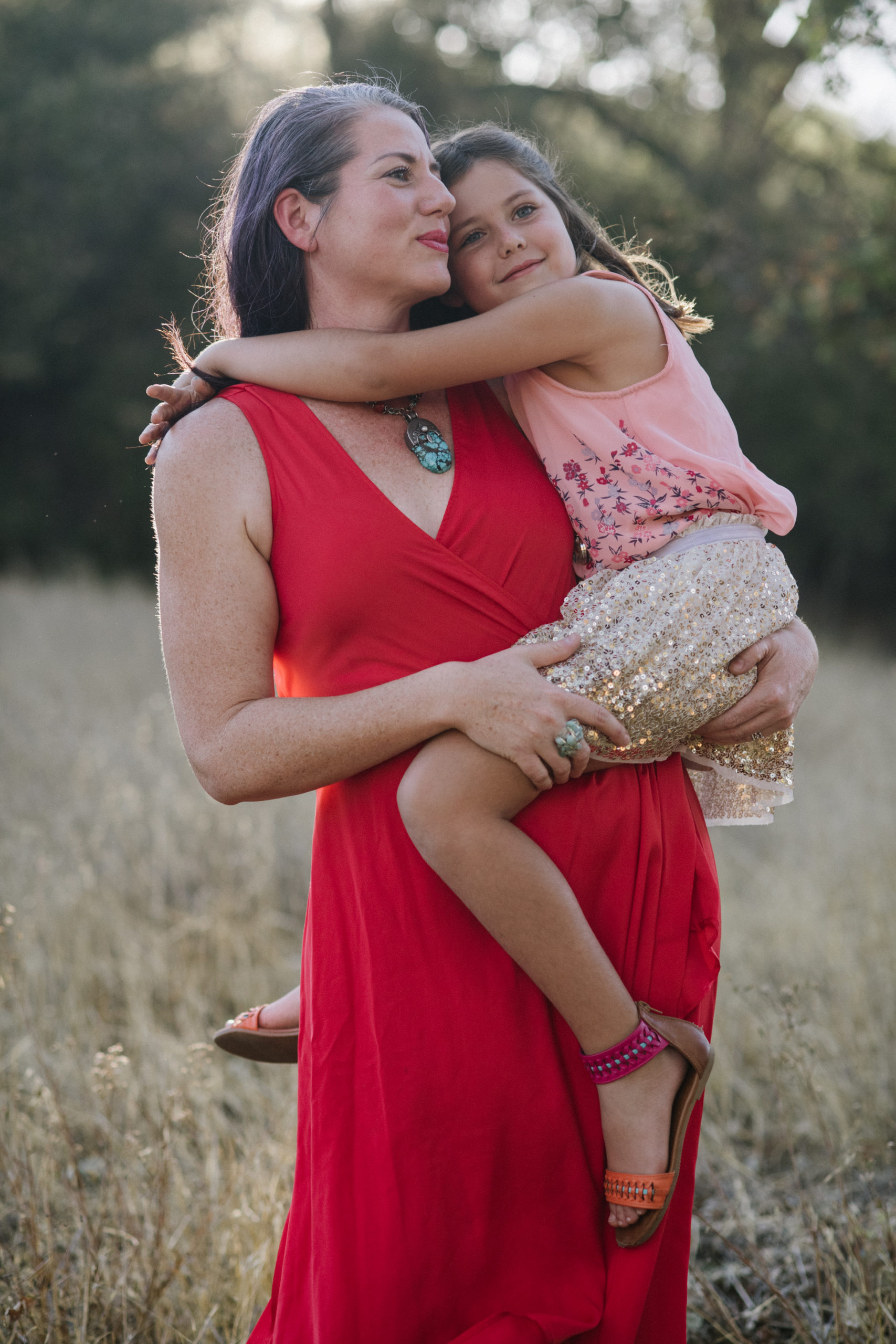 Woman in a red dress holding a child in a field