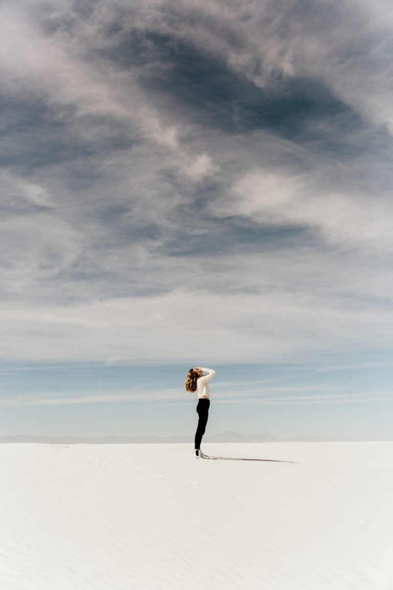 Woman holding her face alone in a dry lake bed