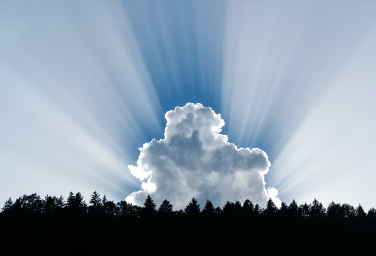 Sun bursting from behind a white cloud