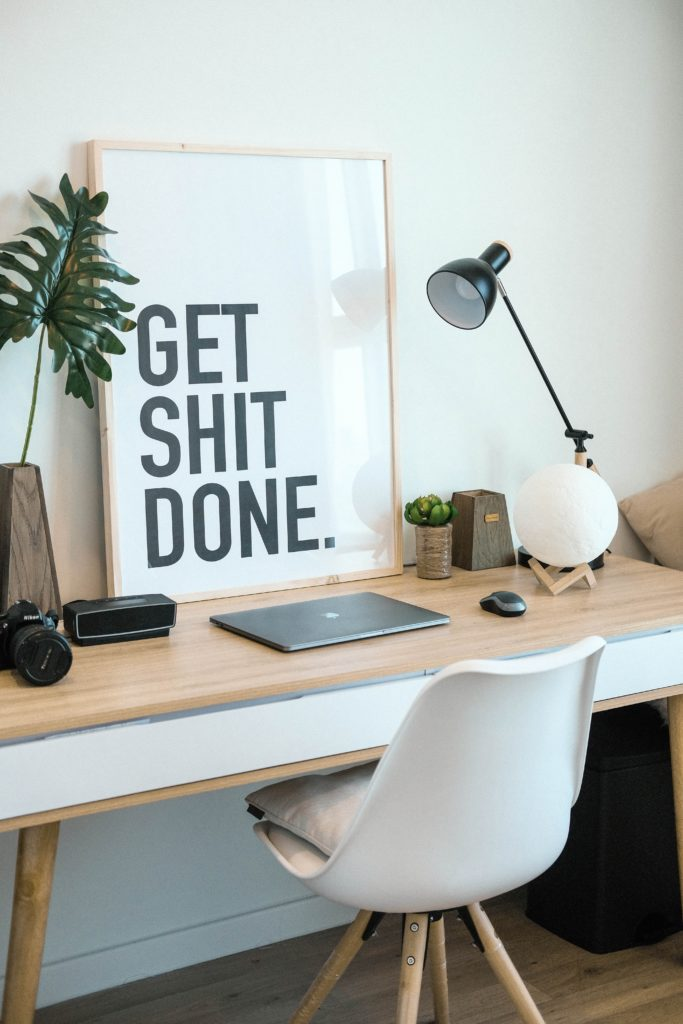 "Modern desk with large poser that reads ""Get Shit Done"""