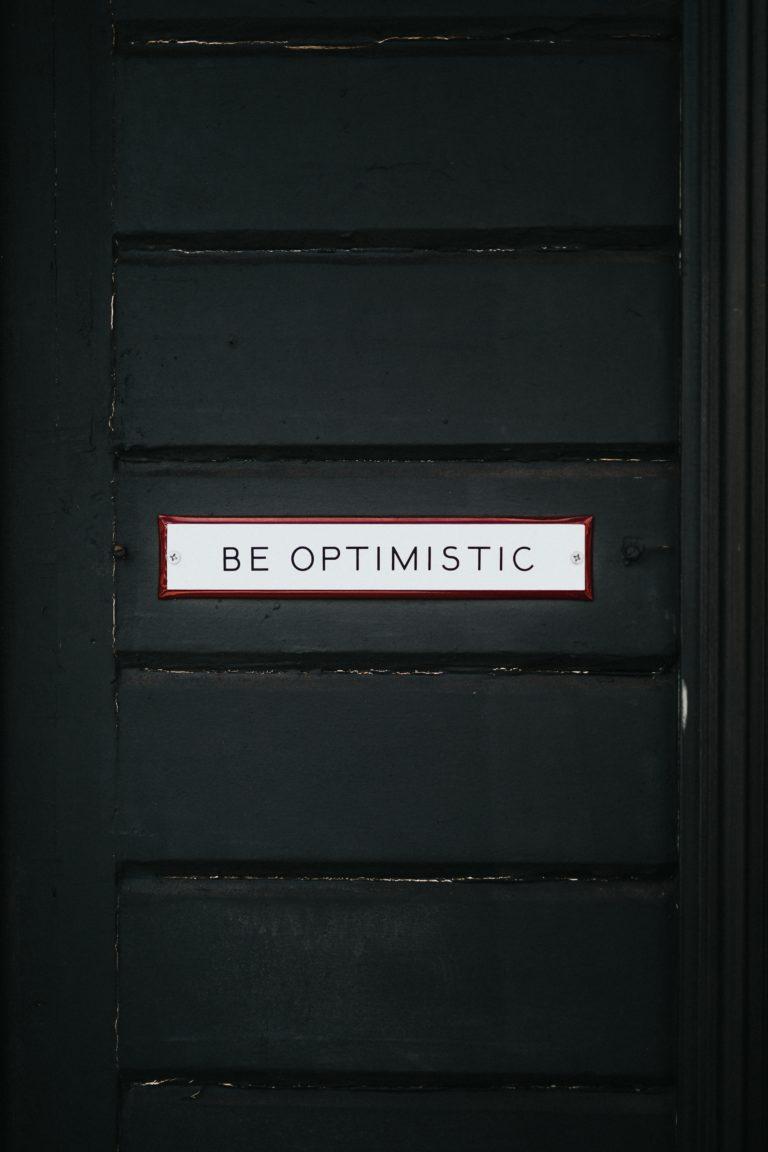 "Black door with sign ""Be Optimistic"""