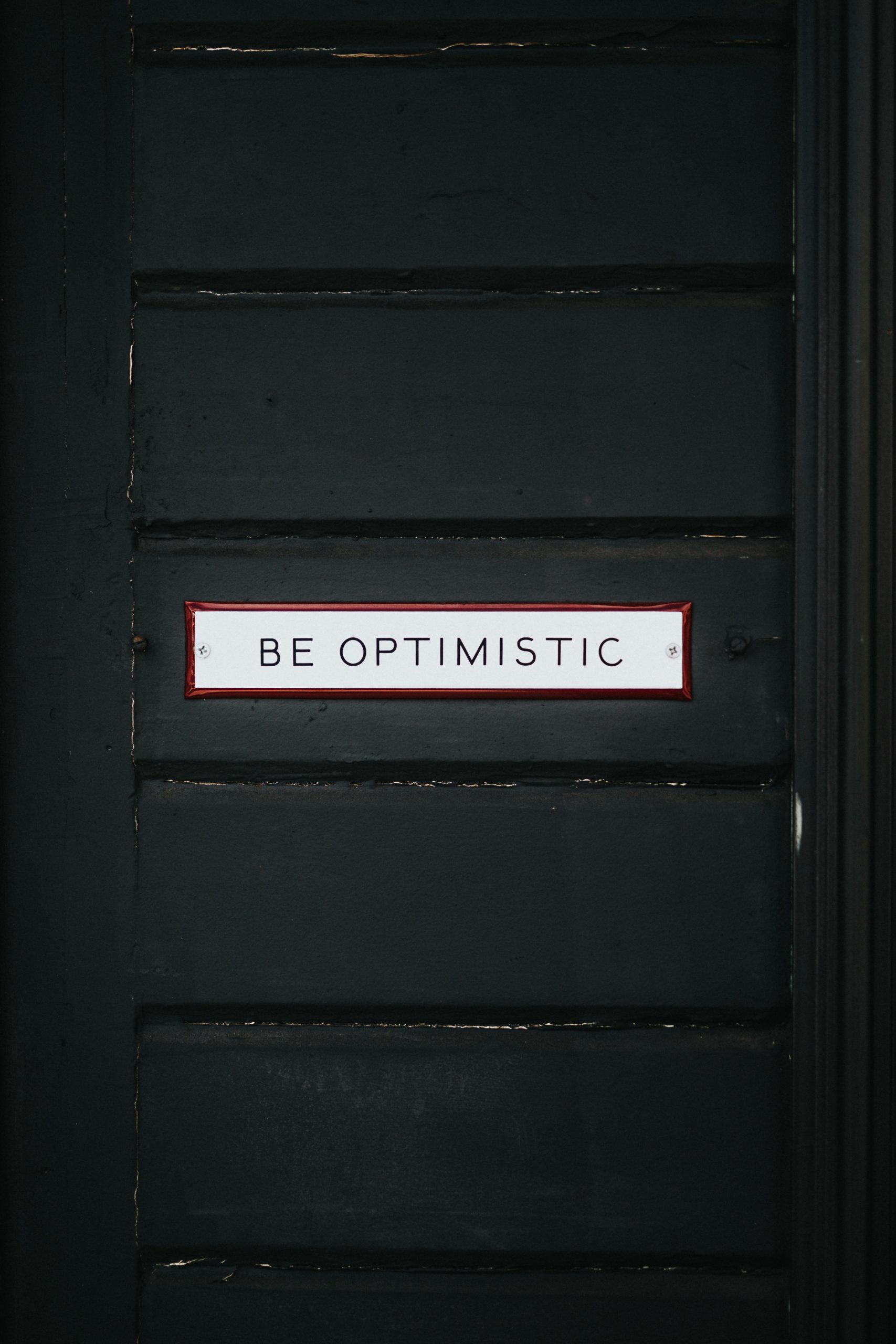 "Black door with sign ""Be Optimistic"""